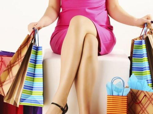 woman sitting down with shopping bags